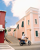 BERMUDA, St. George, man riding scooter on street amid buildings