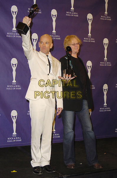 MICHAEL STIPE & MIKE MILLS - R.E.M..The 22nd annual Rock And Roll Hall Of Fame  induction ceremony at the Waldorf Astoria Hotel, New York, New York, USA..March 12th, 2007.full length rem white suit black jacket arm in air award trophy jeans denim .CAP/ADM/BL.©Bill Lyons/AdMedia/Capital Pictures *** Local Caption ***