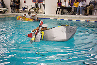 """Alex Penaranda, a senior, pilots his team's boat in the Brooklyn Technical High School Cardboard Boat Regatta in the school's pool in Brooklyn in New York on Friday, March 1, 2013. As part of Engineering Week the teams of students constructed boats made only of cardboard and duct tape. The team's assigned """"captain"""" piloted their boat from one end of the pool to the other and back in a heat with other boats, hopefully without sinking. The surviving boats were timed and the winners received bragging rights with an award also going to the most spectacular sinking. (© Richard B. Levine)"""
