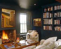 The walls and ceiling of this library have been painted in Hague Blue by Farrow & Ball with plaid curtains and an elegant grey velvet on the sofa and armchair