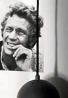 Seen next to a black pendant light in a corner of a living room this black and white photograph of Steve McQueen epitomises the retro cool of the hotel