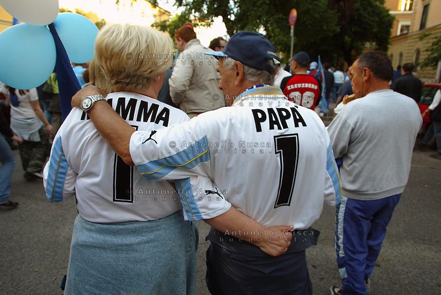 Una copia di tifosi della Lazio con le magliette della loro squadra personalizzate si recano allo stadio Olimpico di Roma