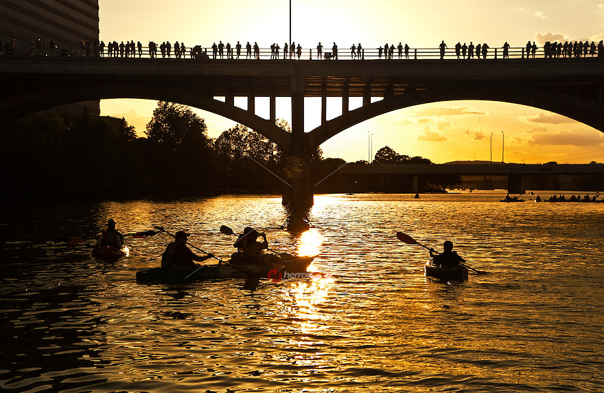 kayakers paddle across a Lady Bird Lake against orange summer sunset as bat watchers gather on the Congress Avenue Bridge in Austin, Texas