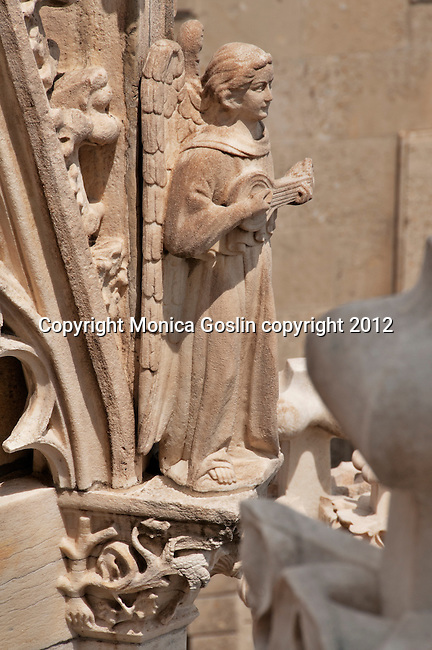 Statue of an angel on Duomo in Milan, Italy which is covered in sculptures and carved stone details