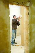 Plastering student applies some smoother plaster over a rough surface, Able Skills, Dartford, Kent.