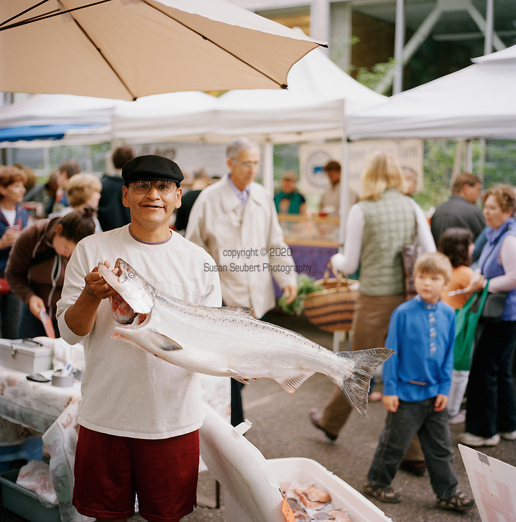 A native American man sells freshly caught salmon at the downtown Portland Farmers' Market in the South park blocks in Portland, Oregon.