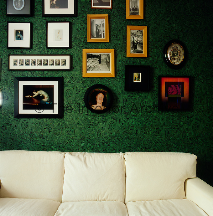 An eclectic mix of artworks hang above a cream sofa in the sitting room where the green and black patterned wallpaper has a neo-pop feel.
