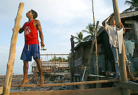 Koh Lanta, Thailand--Two men work on rebuilding a house after a Tsunami destroyed it in the village of Hua Laem on Koh Lanta island, Thailand. Despite the fact that the Thai government is threatening to move the village to another location away from the ocean, many of the  villagers are repairing or rebuilding their original homes.  01/18/05 <br />