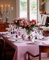 Large bunches of pale pink tulips and roses are used as centerpiece on a laid table with little lanterns used as place setting