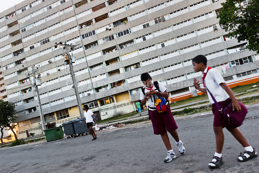"""Cuban school mates walk in front of the large apartment block in Alamar, a public housing complex in the Eastern Havana, Cuba, 12 February 2009. The Cuban economic transformation (after the revolution in 1959) has changed the housing status in Cuba from a consumer commodity into a social right. In 1970s, to overcome the serious housing shortage, the Cuban state took over the Soviet Union concept of social housing. Using prefabricated panel factories, donated to Cuba by Soviets, huge public housing complexes have risen in the outskirts of Cuban towns. Although these mass housing settlements provided habitation to many families, they often lack infrastructure, culture, shops, services and well-maintained public spaces. Many local residents have no feeling of belonging and inspite of living on a tropical island, they claim to be """"living in Siberia""""."""
