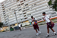 "Cuban school mates walk in front of the large apartment block in Alamar, a public housing complex in the Eastern Havana, Cuba, 12 February 2009. The Cuban economic transformation (after the revolution in 1959) has changed the housing status in Cuba from a consumer commodity into a social right. In 1970s, to overcome the serious housing shortage, the Cuban state took over the Soviet Union concept of social housing. Using prefabricated panel factories, donated to Cuba by Soviets, huge public housing complexes have risen in the outskirts of Cuban towns. Although these mass housing settlements provided habitation to many families, they often lack infrastructure, culture, shops, services and well-maintained public spaces. Many local residents have no feeling of belonging and inspite of living on a tropical island, they claim to be ""living in Siberia""."