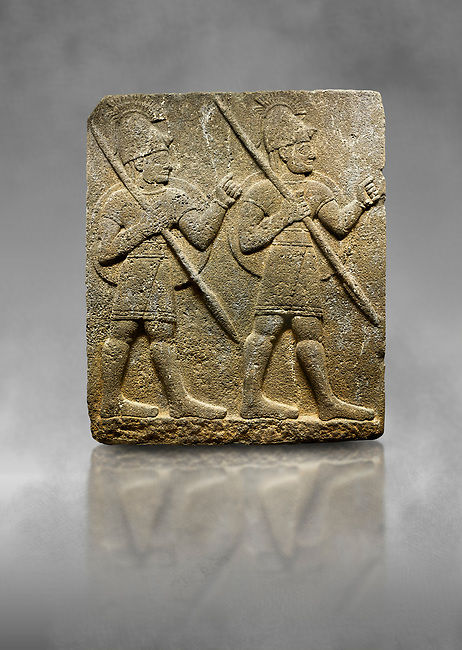 Hittite monumental relief sculpted orthostat stone panel from the Herald's Wall. Basalt, Karkamıs, (Kargamıs), Carchemish (Karkemish), 900-700 B.C. Military parade with soldiers. Anatolian Civilisations Museum, Ankara, Turkey<br /> <br /> Two helmeted soldiers marching soldiers in short skirts carry the shield on their backs and the spears in their hands.  <br /> <br /> Against a grey art background.