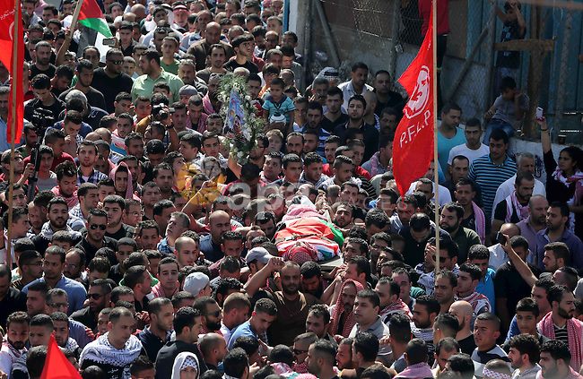 Mourners carry the body of 27-year-old Moataz Zawahra, who was killed by Israeli security forces in the clashes with Palestinian protesters, during his funeral in the West Bank city of Bethlehem October 14, 2015. Israel began setting up checkpoints in Palestinian areas of annexed east Jerusalem as it struggled to stop a wave of attacks that have raised fears of a full-scale uprising. Photo by Muhesen Amren