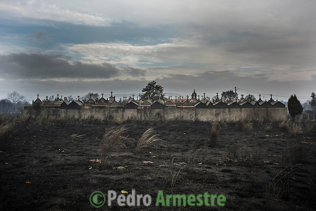 A general view shows a burnt field with a cemetery in background a day after a wildfire in Cualedro, near Ourense on August 31, 2015. A fire broke out on August 30, 2015 around noon in the Cualedro town in Galicia, northwest Spain, affecting at least 3,180 hectares of forest, as seven fires continued to burn in Spain, three in Galicia, one in Cantabria, one in Castile and Leon, one in Catalonia and Extremadura. © Pedro ARMESTRE