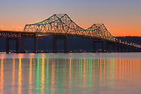 The western sky glows orange after sunset behind the Tappan Zee Bridge, whose lights reflect off the surface of the Hudson River as seen from Tarrytown, New York, USA