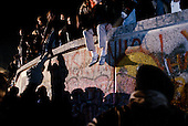 West Berlin, West Germany<br /> November 10, 1989 <br /> <br /> West Germans climb the wall at Brandenburg Gate. Germans gathered at the wall after the East German government lifted travel and emigration restrictions to the West the day before.