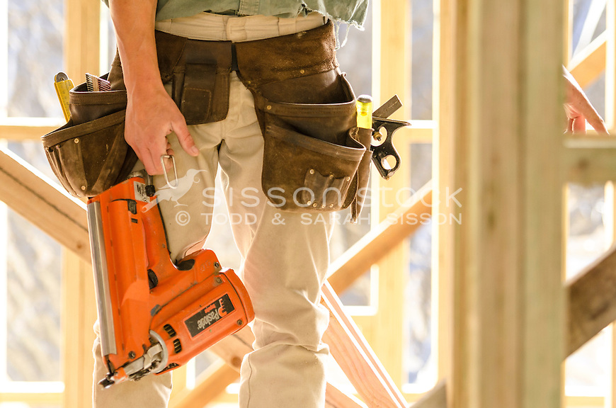 New Zealand Photos | Builder with tool belt on and holding a nail ...