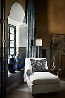 A chaise longue in a neutral fabric is placed in front of a window and makes a pleasant space to relax.