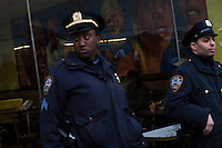 NYPD officers stand guard at the entrance of a McDonald's restaurant while fast food workers protest for Increased their wages in New York, April 04, 2013. Photo by Eduardo Munoz Alvarez / VIEWpress.