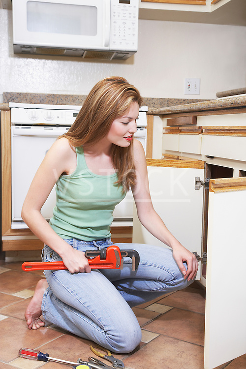 Female plumber fixing kitchen sink