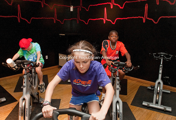 WATERBURY, CT-25 JULY 2012--072512JS02- Chelsea Crane, 10, of Middlebury, along with her brother Nathaniel Crane, 10, left, and Isaac Parker, 12, of Waterbury, work out in a spinning class during the ACHIEVE program Wednesday at the Waterbury YMCA. The group is training for a triathlon. .Jim Shannon Republican-American