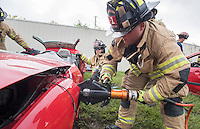 NWA Democrat-Gazette/J.T. WAMPLER Rogers firefighter Jacob Thompson cuts Wednesday Sept. 9, 2015 through a vehicle's frame during extrication exercises. The department does similar training  throughout the year as opportunities allow. The training allows firefighters to try out new techniques and keep familiar with the equipment used to remove vehicle occupants after accidents.