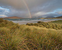 Rainbow shines above sea and coastal sand dunes at Seilebost beach, Isle of Harris, Scotland