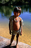 Mato Grosso, Brazil. Young Rikbaktsa (Canoeiro) Indian boy standing on an upturned dugout canoe by the river.