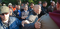 Sandor Pinter (C) minister of internal affiars surrounded by bodyguards attends an anti-government rally of firemen and other law enforcement workers who protest in front of the Parliament against the government's austerity measures in Budapest, Hungary on May 06, 2011..The government has launched a package of fiscal reforms to cut the budget deficit, including scrapping early retirement, which mostly affects law enforcement personnel. ATTILA VOLGYI