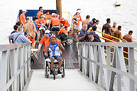 Lifeguards, athlete handlers, and other safety officials man the exit of the swimming leg of the course, as Minda's handlers Shawn and Rob push her up the exit ramp in her wheelchair to start the second leg of the Aquaphor New York City Triathlon in New York on July 8, 2012.