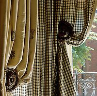 Carved wooden finials hold back embroidered floral curtains and contrasting black and white gingham under-curtains