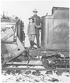 A rather close-in view of a man and a boy standing on the tender apron of a wrecked locomotive.  It is the same wrecked engine as shown in RD094-007.<br /> D&amp;RG (?)