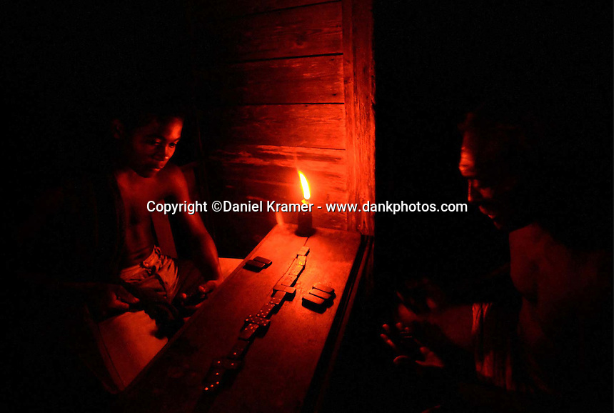 In Eastern Cuba a man plays dominos by candlelight with his grandson. (2000)