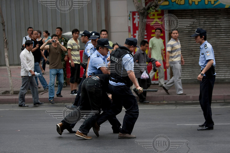 Police arrest a Han Chinese man who was part of a mob that chased down a Uighur in Urumqi. They caught up with the Uighur and beat him before the police intervened firing shots in the air and arresting the two Han attackers. The mob then attacked the police to try and stop the arrests. Ethnic violence between the Uighur and Han people had erupted in the city a few days earlier.