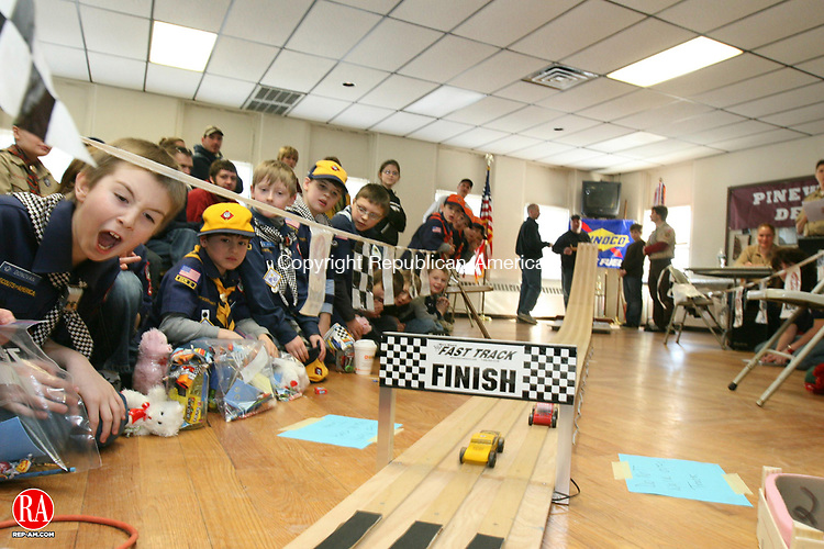 "WINSTED, CT - 31 January, 2009 - 013109MO01 - Cub Scout Donovan Brown, 8, far left, watches a heat finish during the annual Pack 27 Pinewood Derby at the Elm Street firehouse Saturday. Cub scouts and their families work together to fashion race cars each year from blocks of wood, nails and wheels. ""They love it,"" said derby Chairman Rob Pac. ""It's a good bonding experience."" Jim Moore Republican-American."