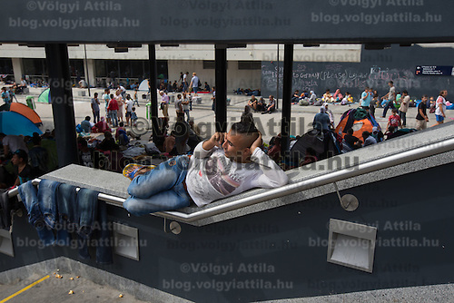 Illegal migrant talks on the phone in the transit zones in front of the main railway station Keleti in the hopes to leave for Germany in Budapest, Hungary on September 03, 2015. ATTILA VOLGYI