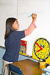 Vietnamese American seven year old girl in school uniform writes numbers and measurements on white board in classroom in New Orleans