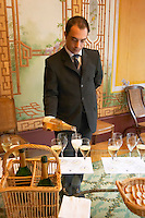 In the tasting room a waiter pouring champagne for a tasting at Champagne Deutz in Ay, Vallee de la Marne, Champagne, Marne, Ardennes, France, low light grainy grain