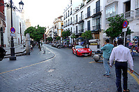 A red Ferrari adds color to a street scene in Seville, Spain