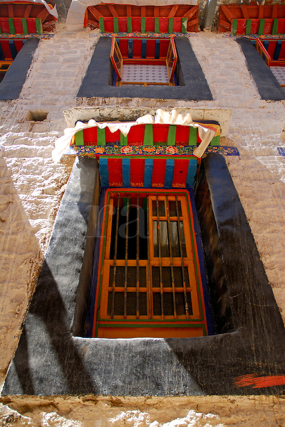 Typical traditional Tibetan sloping window architecture, with brightly painted frame, and overhang with black trapezoidal surround, Barkhor area of Lhasa, Tibet.