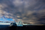 Iceberg, Antarctica, with brooding clouds..