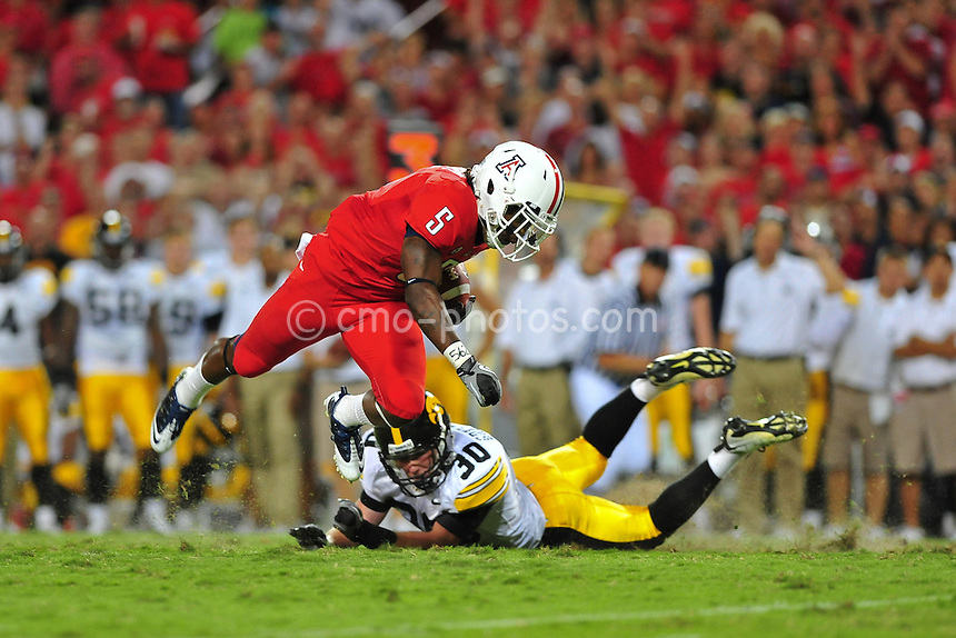Sept 18, 2010; Tucson, AZ, USA; Arizona Wildcats running back Nic Grigsby (5) is tripped up by Iowa Hawkeyes cornerback Brett Greenwood (30) in the 2nd quarter of a game at Arizona Stadium.