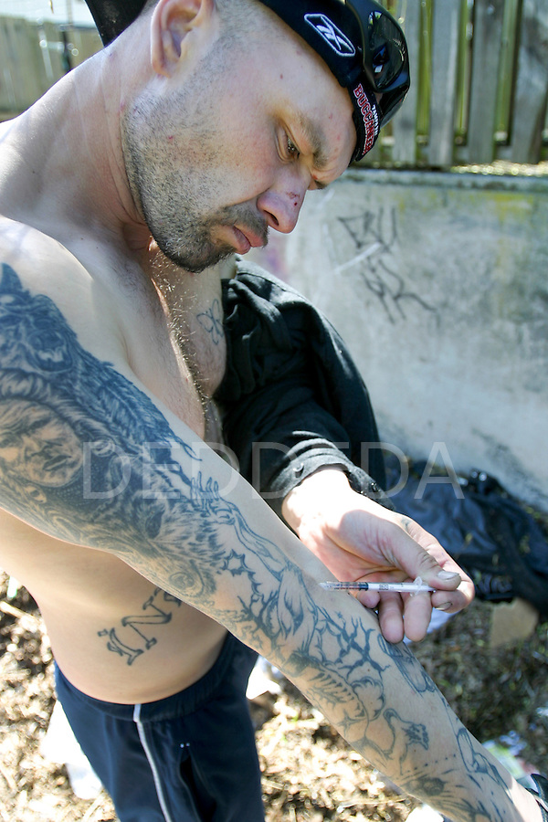 A man who goes by the name Kyzr, injects his fix of morphine mixed with cocaine and synthetic heroin in a vacant lot along Mason Street in Victoria, B.C. The vacant lot, littered with garbage and used needles, is a common site for intravenous drug users to utilize as a shooting gallery. Photo shot for the GLOBE and MAIL.
