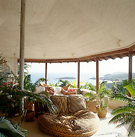 A sunny terrace, furnished with light wicker seating and palm trees, has views over the Mustique coastline