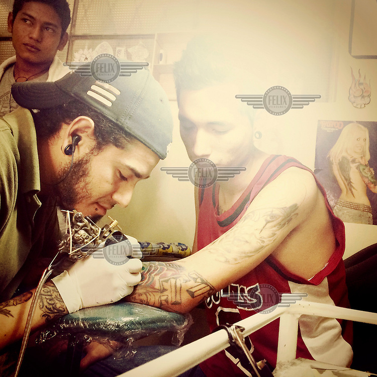A tattooist inks a design on the forearm of a youth in the local tattoo parlour in Tumbaco.