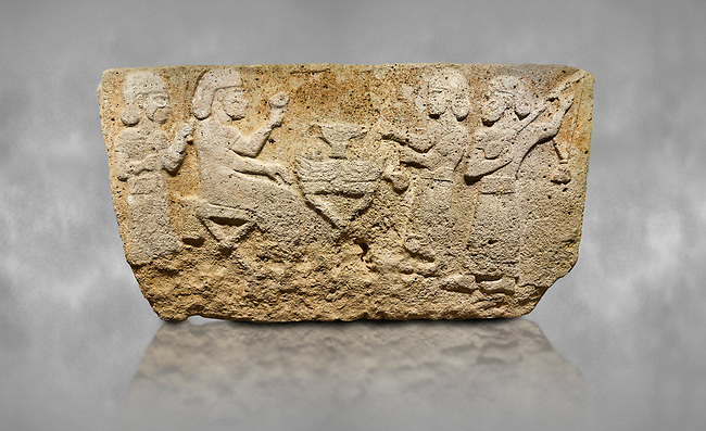 Hittite monumental relief sculpted orthostat stone panel from Water Gate Limestone, Karkamıs, (Kargamıs), Carchemish (Karkemish), 900-700 BC.  Anatolian Civilisations Museum, Ankara, Turkey.<br /> <br /> The figure sitting on a stool to the left of the table holds a goblet in his right hand which he raised upwards. Behind, there is a servant with a fan in his hand. On the other side of the table is another servant waits with a vessel in the hands. The rightmost figure plays a Saz (a stringed musical instrument) with the tassel on the handle. <br /> <br /> On a grey art background.