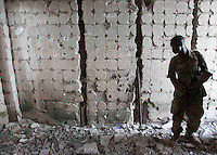 A member of the Somali National Army conducts a search of the damaged Somali Parliament building after an attack led by al-Shabaab militants.