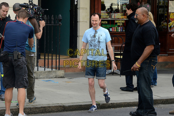 Mark Gatiss<br /> Filming on the set of &quot;Sherlock&quot;, London, England.<br /> August 21st, 2013<br /> film actor actors acting  full length blue t-shirt cut offs jean jeans denim shorts camera <br /> CAP/IA<br /> &copy;Ian Allis/Capital Pictures