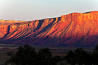 Drenched in sunset light, red cliffs tower over Paradox Valley in southwestern Colorado's high desert.