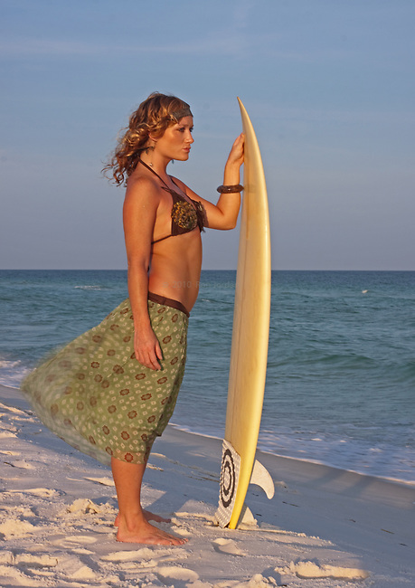 Surfer girl. Woman wearing sarong and bikini holding surfboard gazing into the ocean surf on beach.
